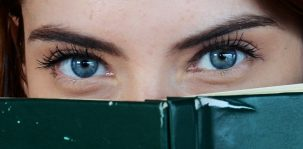 Redaktionsmanagement: Frau schaut neugierig über den Rand eines Buchs