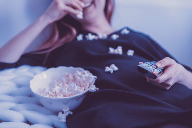 Artikelbild YouTube SEO: Frau mit Fernbedienung isst Popcorn