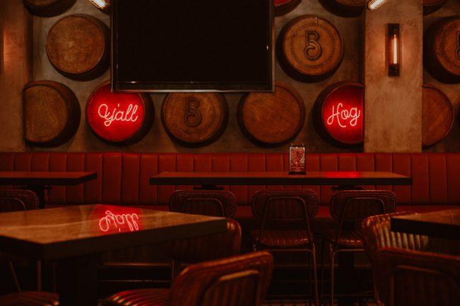 Pub mit leeren Stühlen und Tischen, Bierfässern an der Wand und einen großen Screen