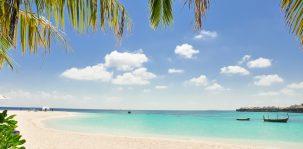 Strand mit Palmen, weißem Sand, türkisblauem Meer, ein paar Quellwolken und einem Boot im Wasser